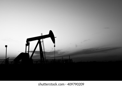 Sunset and silhouette of crude oil pumping unit in oilfield - black and white