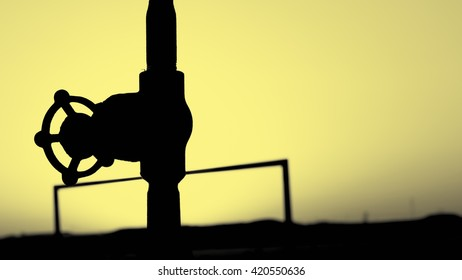 Sunset and silhouette of a gate valve in the oilfield - ambrotype edit image