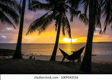 Sunset silhouette of man drinking bottle of rum on tropical Guyam Island, part of Siargao, Mindanao - Philippines