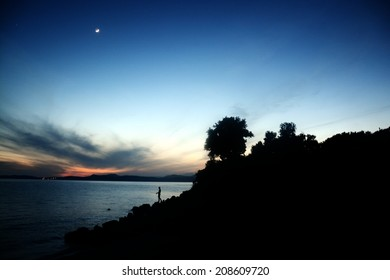 sunset silhouette of man fisshing