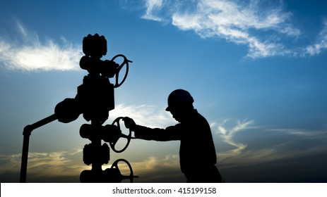 Sunset and silhouette of oilfield worker monitoring wellhead controls in oilfield