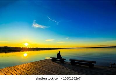 Sunset silhouette on lake pier landscape - Shutterstock ID 1050188267