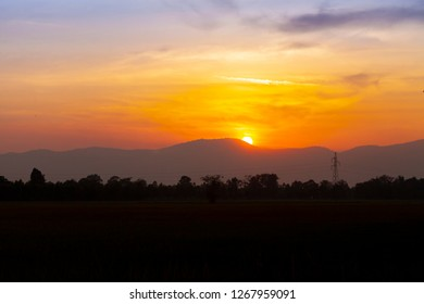 Sunset silhouette on mountain and have high voltage pole . landscape image of countryside for wallpaper or background