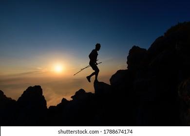 Sunset silhouette of skyrunner man climbing alpine ridge with poles