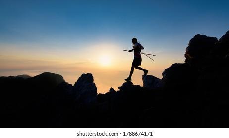 Sunset silhouette of skyrunner man descending from alpine ridge with poles