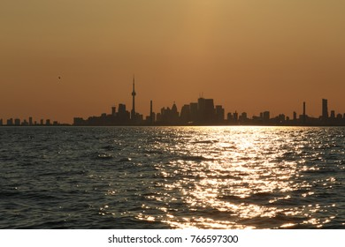 Sunset silhouette of Toronto City Skyline from the water.