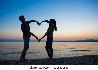 sunset silhouette of young couple in love holding hands at beach