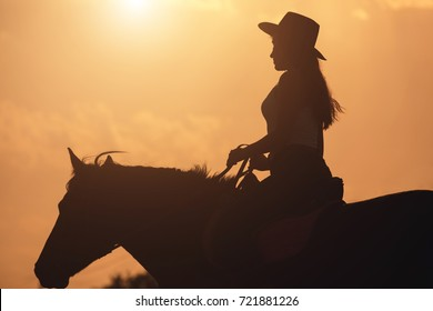 Sunset silhouette of young cowgirl in hat riding her horse