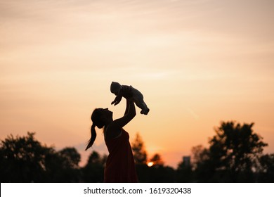 Sunset Silhouette: Young mother holding her baby boy child in city park standing in front of setting sun and vivid orange sky - Family values warm color summer scene handheld
