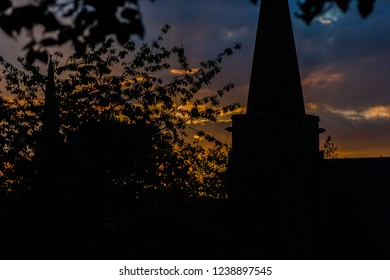Sunset with a silhouetted church steeple and tree, landscape orientation