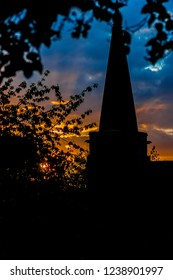 Sunset with a silhouetted church steeple and tree, portrait orientation