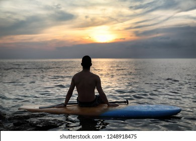 Sunset Silhouette-Rear View Of Young Handsome Man Sitting On Surfboard In The Open Sea Looking At Horizon At Beautiful Scenic Sunset