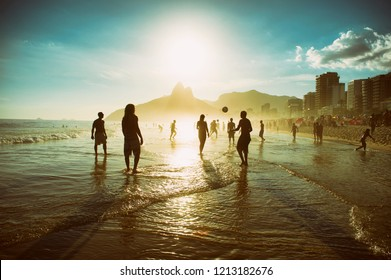 Sunset silhouettes of people playing in a football keepy-uppy circle, known locally as altinho, in the waves on Ipanema Beach in Rio de Janeiro, Brazil