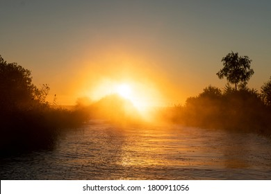 Sunset sky background. Gold sunset sky with evening sky clouds over the lake with fog.Crystal clear water texture. Small waves with water reflection - Shutterstock ID 1800911056