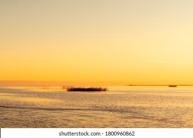 Sunset sky background. Gold sunset sky with evening sky clouds over the lake with fog.Crystal clear water texture. Small waves with water reflection - Shutterstock ID 1800960862