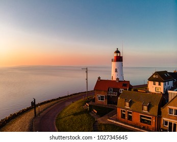 Sunset sky by the lighthouse of urk on the rocky beach at the lake Ijsselmeer by the former island Urk Flevoland Netherlands, Bird eye view drone view