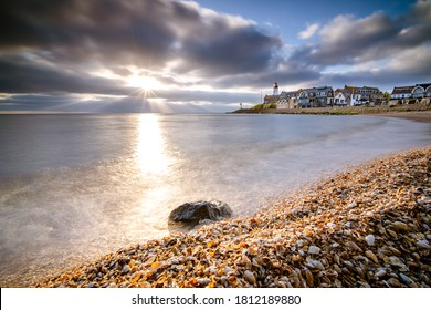 Sunset sky by the lighthouse of urk on the rocky beach at the lake Ijsselmeer by the former island Urk Flevoland Netherlands