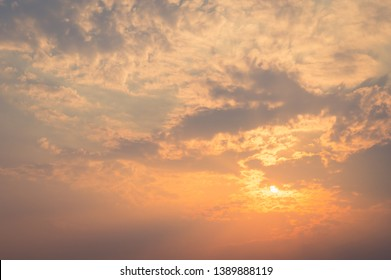 Sunset sky and cloud background .Cumulus sunset clouds with sun setting down .Texture of bright evening sky during sunset  with cloudy and yellow orange sundown