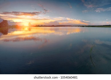 Sunset sky with clouds above lake. Beautiful sunny landscape.