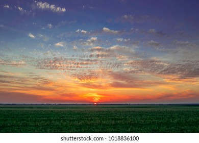 sunset sky with clouds and meadow