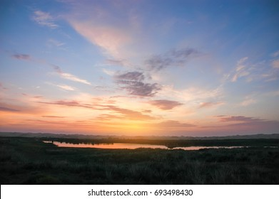 Sunset sky clouds.Countryside Landscape Under Scenic Colorful Sky At Sunset Dawn Sunrise. Sun Over Skyline, Horizon. Warm Colours.