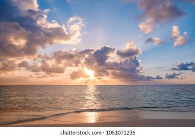 sunset sky with colorful clouds over ocean and beach -