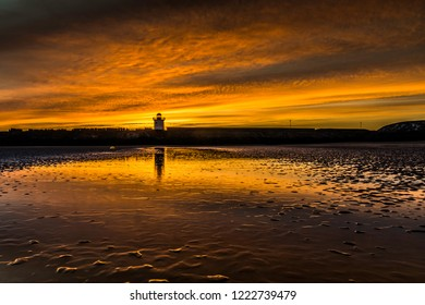 Sunset sky and colourful reflections in the water on the beach at Burry Port, Carmarthenshire. Wales. UK. Silhouette of a lighthouse in the background.