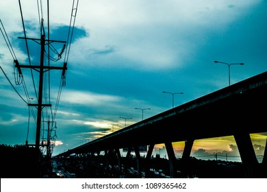 the sunset sky with the flyover and eletric post