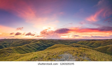 Sunset sky, green grassland. Panorama. Sumba, Indonesia. Magnificent scene the meadow on the colorful sunset sky background. The beauty of Sumba island, Indonesia. Idyllic place for relax.