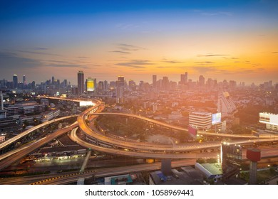 Sunset sky over city business downtown and highway intersection, cityscape background