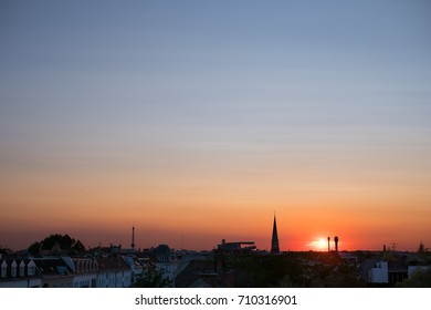 sunset sky over city - colorful sky panorama over rooftops