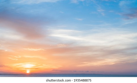 Sunset sky over sea in the evening with colorful orange sunlight background.