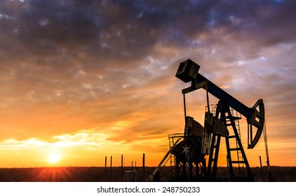 Sunset sky with profiled oil well