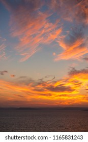 Sunset sky as watercolor above the sea, vertical. Nature, weather, atmosphere, travel theme.