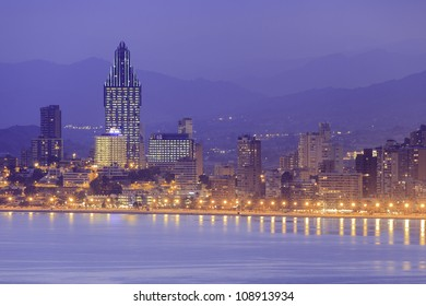 Sunset skyline of the Mediterranean coastal resort of Benidorm, Spain showing high-rise apartment and hotel buildings.