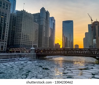 Sunset and skyscrapers reflecting off of the icy surface of the Chicago River after winter storm