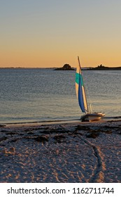 At sunset a small sailing boat rests at the beach at the waters edge.