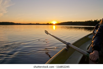 Sunset and a small wooden boat with people
