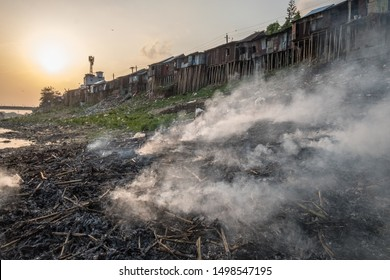 At sunset, smoke rises from burning garbage on the banks of Sylhet's Surma River, Bangladesh with riverside homes built on bamboo stilts.