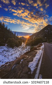 Sunset at snow-covered Mount Baldy in winter with a road winding through the tall peaks and colorful clouds in the sky, San Gabriel Mountains, San Bernardino County, California