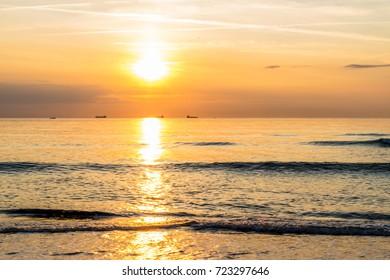 Sunset soft beautiful ocean wave on sandy beach. romantic travel background.