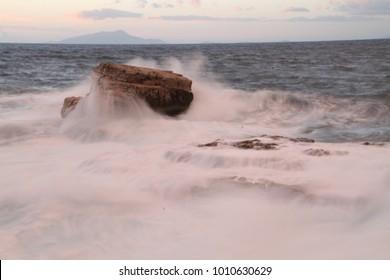 Sunset in Sorrento, Italy. Sea waves, rocks and sun light. Mediterranean sea.