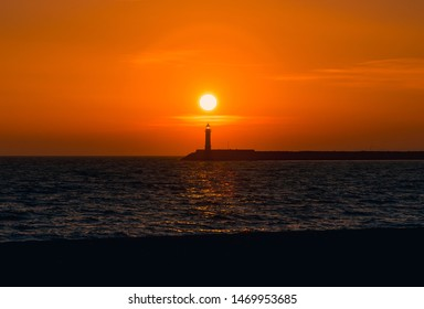 Sunset in Almería, Spain, with an orange sky just above a lighthouse