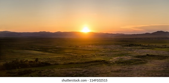Sunset in steppe. Blinding sun. Sunset in hills. Sun and hills. Open space. Far.