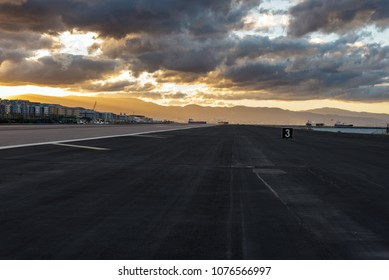Sunset with stormy clouds over airport runway in Gibraltar