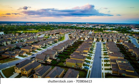 Sunset Suburb Rows of Houses and Homes line a Modern Neighborhood. Aerial Drone view above Austin , Texas , USA rooftops and suburbia layout