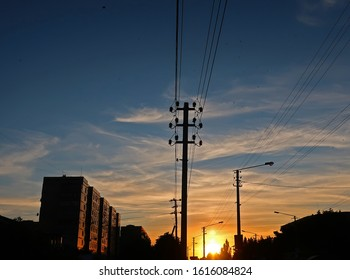 The sunset sun on a blue sky above the city shines on houses and power poles