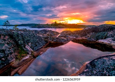 Sunset sun The stones reflect the rays of the sun. Wild nature. Stony shore. Northern nature. Karelia. The nature of Russia. Republic of Karelia. Ladoga lake.