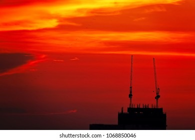 sunset sunlight red sky silhouette construction building tower crane