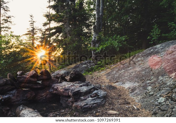 Sunset with Sunrays on top of a mountain in the bavarian forest with stones in front of